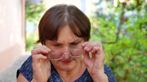 Portrait of elderly woman with eyeglasses has eyesight problems Live Action