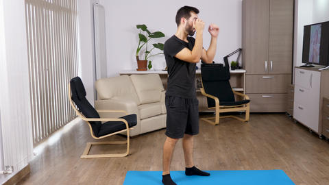 Athletic man kicking and punching in the living room Footage