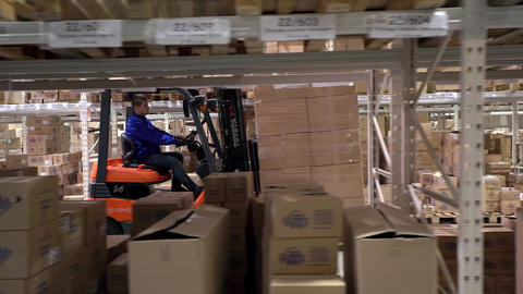 Forklift Truck Driver in a Factory or Warehouse Driving Between Rows of Shelving Footage