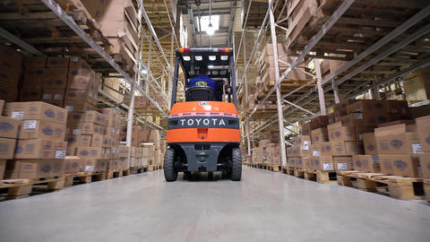 Forklift Trucks Move Between Large Metal Shelves at a Modern Warehouse and Unloa Footage
