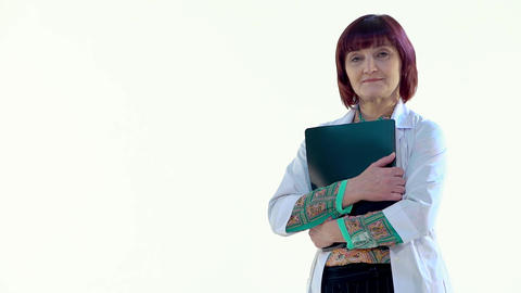 Female Doctor Hugging a Black Folder and Looking at the Camera, Laughing Footage