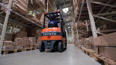 Logistics business and shipping facility with manual worker operating forklift t Footage