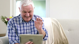 Old man using video chat on tablet Live Action