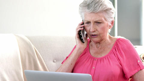Old woman on a phone with her computer Footage