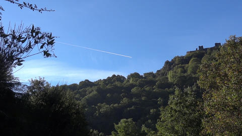 Condensation trail left by a jet on blue sky above a fortress built in the woods Footage