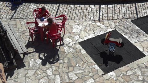 Women sitting at a table plastic red seated on the terrace and write letters to  Footage