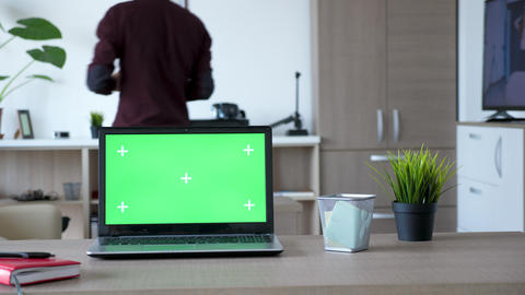 Modern laptop with an isolated green screen chroma mock up on the table Live Action