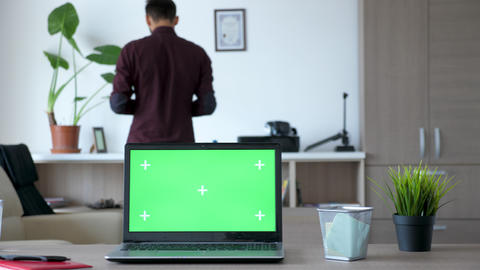 Laptop with an isolated chroma green screen on the desk Live Action