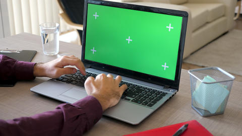 Top view of man in his house working on a laptop with a green screen chroma mock Live Action