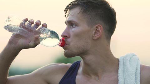 Thirsty sportsman drinking water, refreshing and restoring water balance Footage