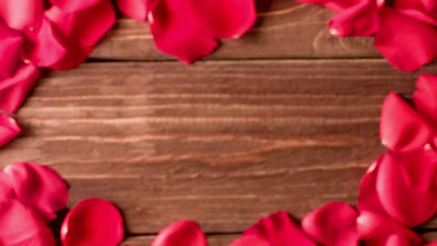 Red rose petals scattered on the wooden floor Live Action