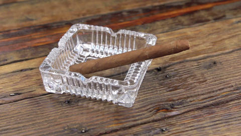 Luxurious cigar in an ashtray on a vintage wooden table. Slider shot Footage