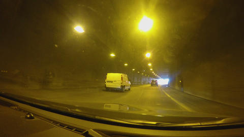 Cars driving towards light at dark tunnel end at high speed, travel by auto Live Action