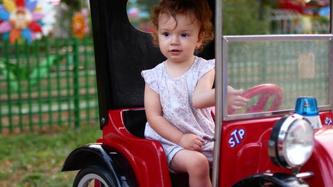 Child girl and rides an electric car in the park for entertainment. Attractions Footage