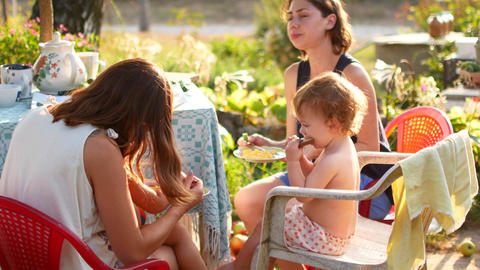 Girlfriends feed their young children in the fresh air. House in the village Live Action