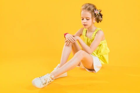 A teenage girl is sitting on a yellow background フォト