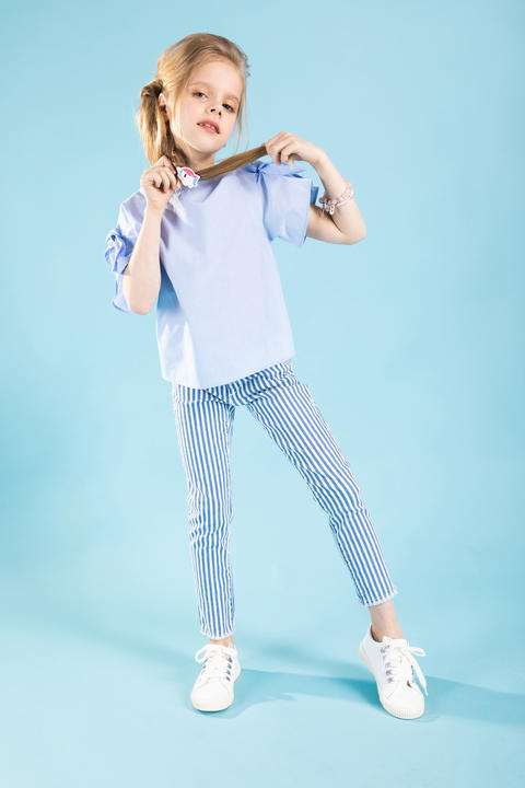 Full-length portrait of a beautiful girl in blue clothes on a blue background フォト