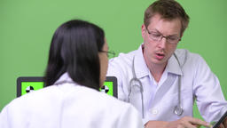 Young Asian woman doctor having meeting with young man doctor Footage