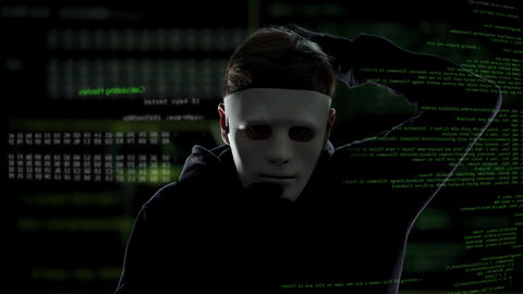 Unrecognizable man in white mask staring into camera, data codes background Footage