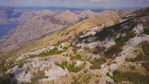 Winding road in rocky mountains and view on Kotor Bay. Sunny day in Montenegro GIF