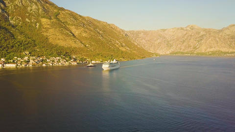 Luxury cruise ship floats in sea bay against sunny mountains. Aerial view of GIF