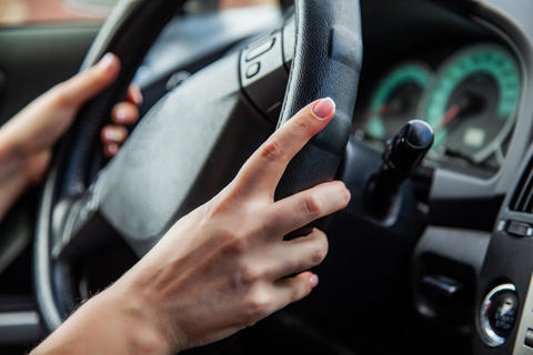 A woman is driving, women's hands are on the handlebars Photo