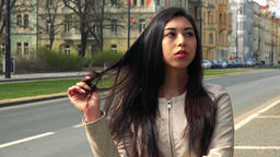 A young Asian woman is bored and plays with her hair in the middle of a street Footage