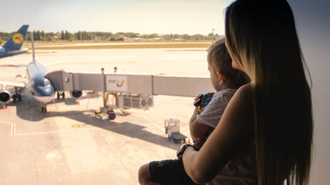 Toned portrait of young mother with child looking on airplanes at airport フォト