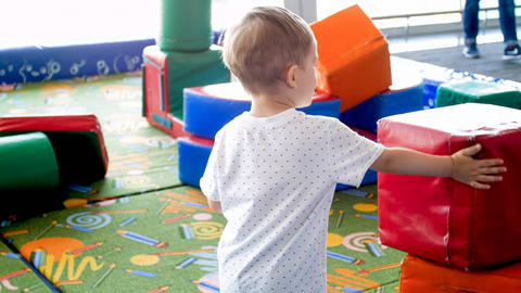 Cute toddler boy playing on indoor playground with soft blocks Photo