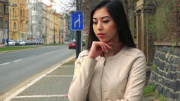 A young Asian woman broods while walking back and forth in a street in an urban Footage