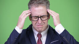 Studio shot of stressed mature businessman having headache Footage