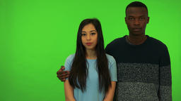 A young black man and a young Asian woman look at the camera, his arm around her Footage