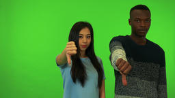 A young black man and a young Asian woman show thumbs down to the camera - green Live Action