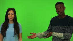 A young Asian woman and a young black man present something - green screen Footage