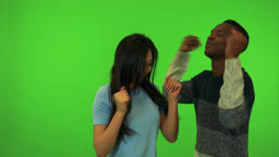 A young Asian woman and a young black man celebrate - green screen studio Footage