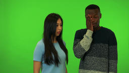 A young Asian woman and a young black man argue - green screen studio Live Action