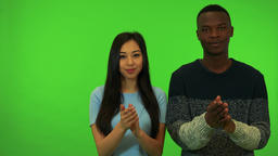 A young Asian woman and a young black man applaud and nod their heads Footage