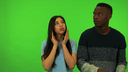 A young Asian woman and a young black man cover their faces with their hands, Footage
