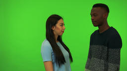 A young Asian woman and a young black man hug and talk - green screen studio Live Action