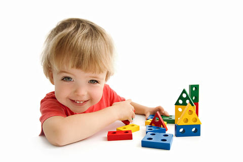 Cute boy building house isolated on white Photo