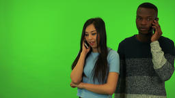 A young Asian woman and a young black man talk on their smartphones - green Live Action
