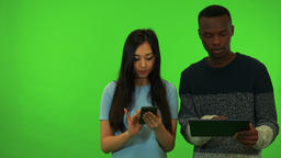 A young Asian woman and a young black man work on a smartphone and a tablet, he Live Action
