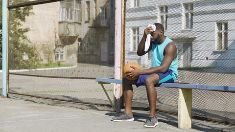 Sad Afro-American male sitting on the bench and playing ball, loneliness Footage