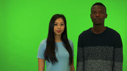 A young Asian woman and a young black man nod at the camera - green screen Footage