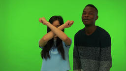 A young Asian woman and a young black man protest to the camera - green screen Live Action