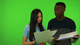 A young Asian woman and a young black man hold papers, she explains something to Live Action