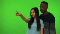 A young Asian woman and a young black man point at and talk about their Footage
