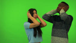 A young Asian woman and a young black man cover their ears from an unpleasant Live Action