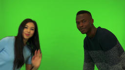 A young Asian woman and a young black man lean into the shot and wave at the Footage
