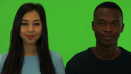 A young Asian woman and a young black man smile at the camera - closeup on the Live Action